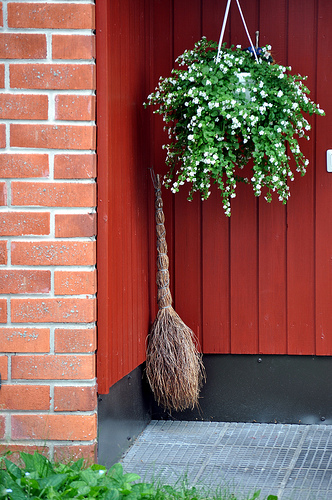 A red cubby with a broom and hanging pant