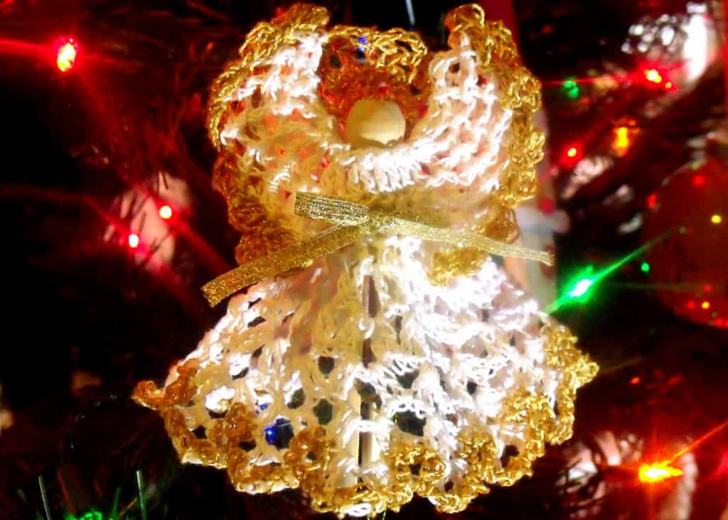 A gold trimmed crochet angel in a Christmas tree