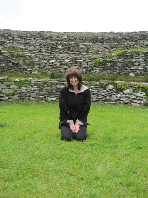 Woman on her knees in the center of a stone fort in Ireland