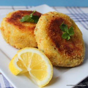 Two cod fish cakes on a plate with lemon wedges