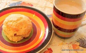 A raisin scone on a plate beside a cup of tea