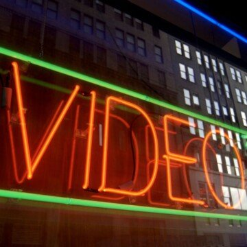 A red neon video sign in a window