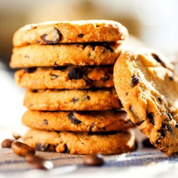 Chocolate chip cookies in a stack with one leaning against the stack