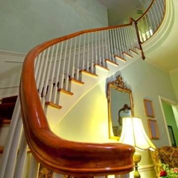 A winding stairway with a shining wooden bannister