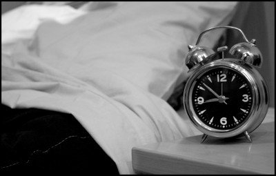 A black and white photo of an alarm clock beside a bed