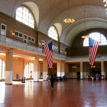 Two large American flags flying over the Great Hall on Ellis Islan