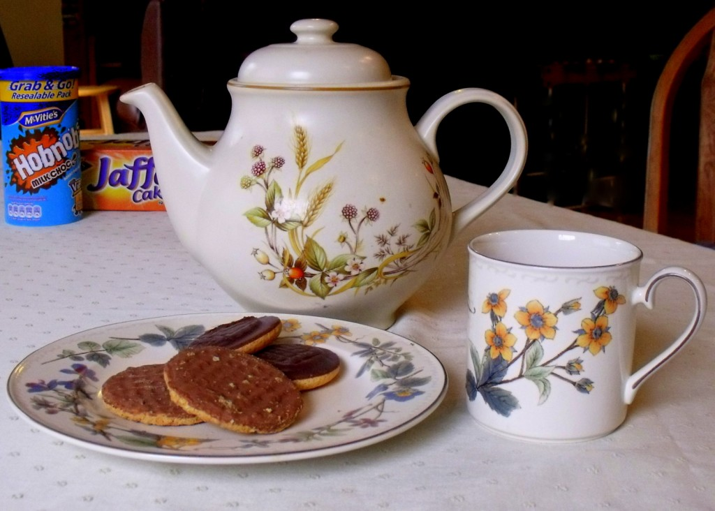 A tea pot with a floral mug and a plate of biscuits