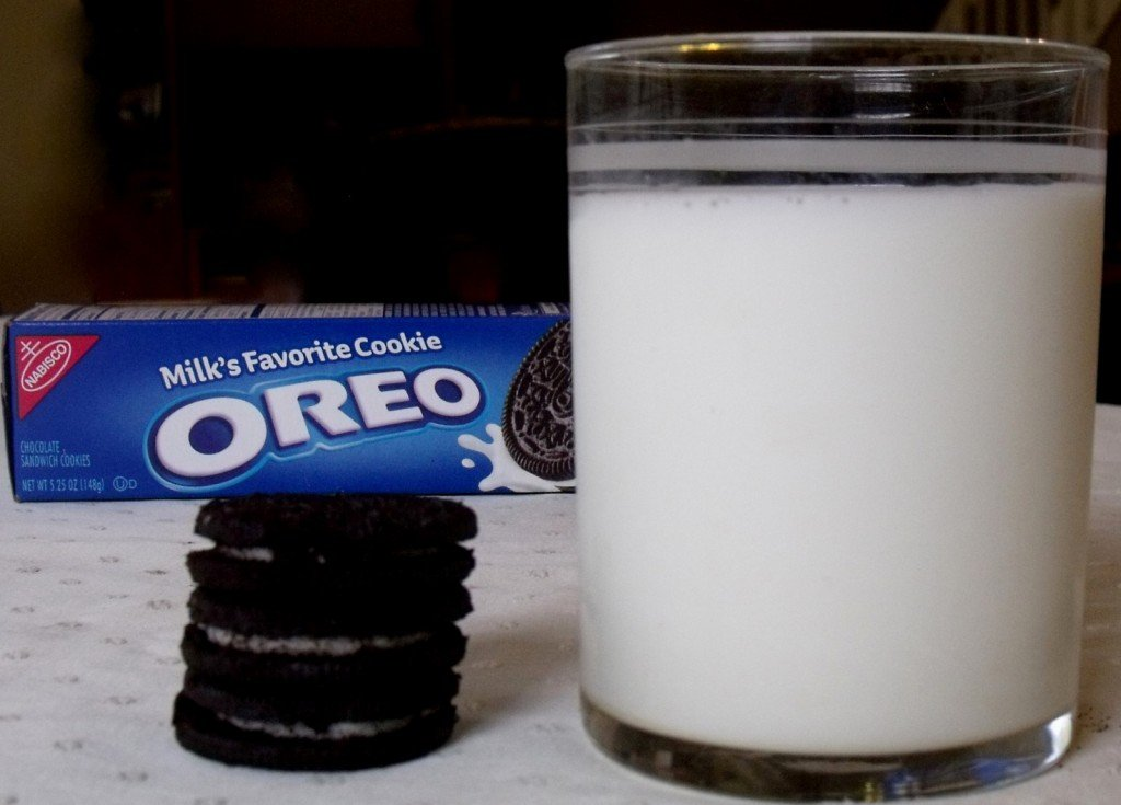 A large glass of milk with a stack of three oreo cookies