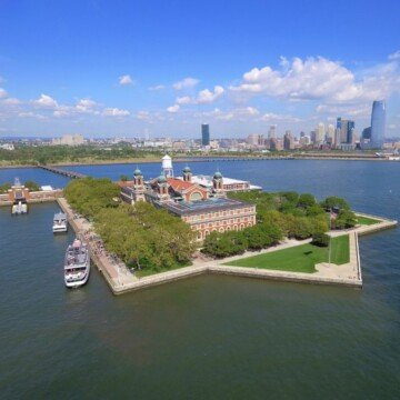 An aerial view of Ellis Island with the New York City skyline across the water in the distance
