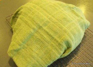 Bread loaf wrapped in a clean dish towel to soften the crust