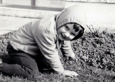 Black and white photo of a child kneeling in the grass