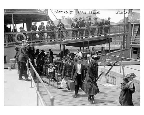Vintage image of immigrants leaving a boat by a wooden walkway