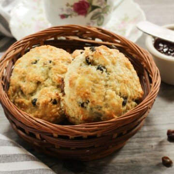 Two raisin scones in a basket beside a china cup of tea and jam