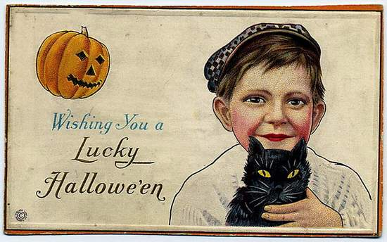 A vintage greeting showing a boy with cap holding a black cat