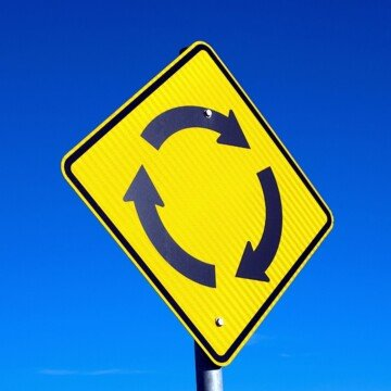 Yellow road sign with arrows going in a circle against a blue sky