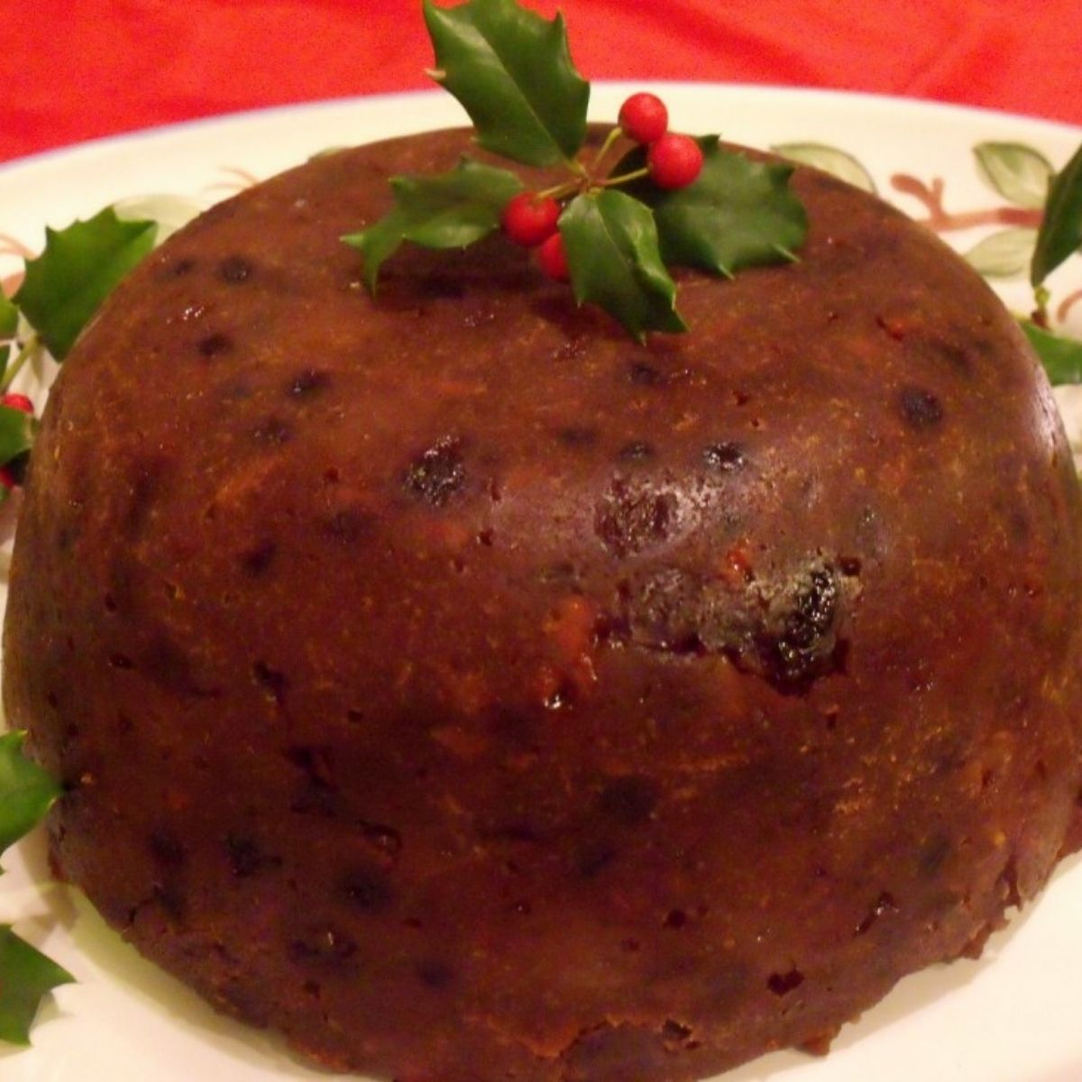 A brown Christmas pudding on a platter with holly on top as a decoration