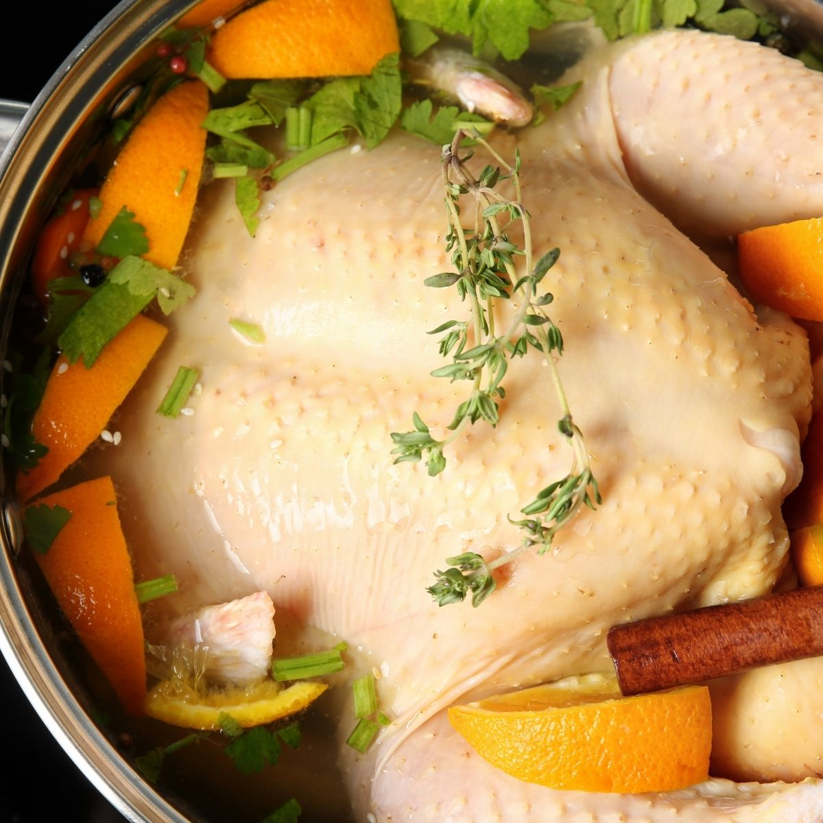 An uncooked turkey in a pot with vegetables and herbs for brining
