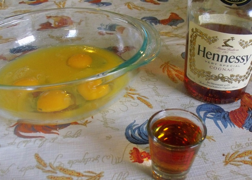 Brandy in a shot glass beside a bowl of eggs and bottle of Brandy