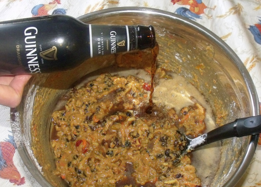 Guinness porter or stout being added to plum pudding mixture in a bowl