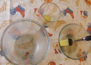 brushing melted butter in pudding bowls