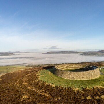 Aerial view of a stone ring fort on a green and brown hilltop under blue skies