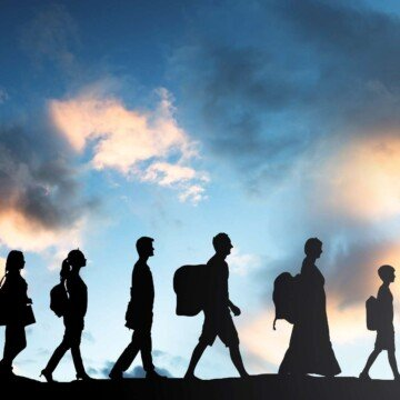 A line of people in silhouette walking against a cloudy sky backdrop