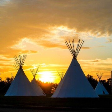Native American tee pees with the sun setting