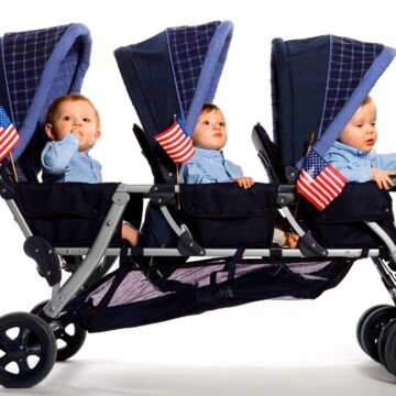 Three babies in a triplet stroller with American flags