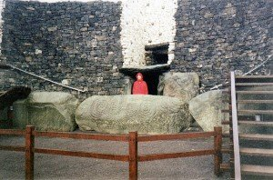 A person stands at the entrance to Newgrange