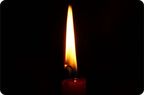 A candle flame highlighted by a black background