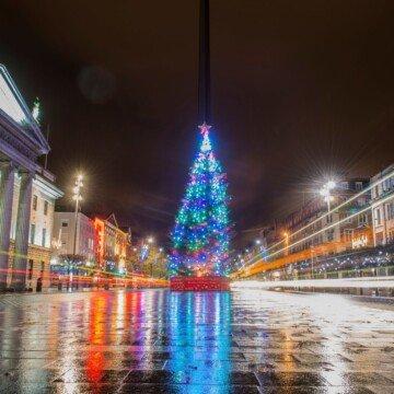 A blue illuminated Christmas tree reflects on a wet city street