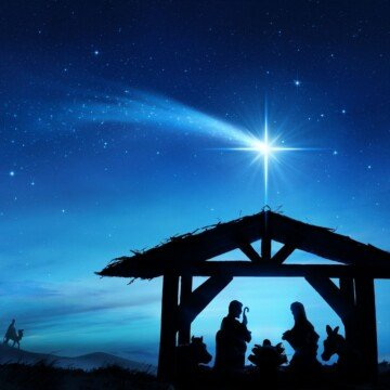 Night sky with a star over a silhouette of a stable nativity scene