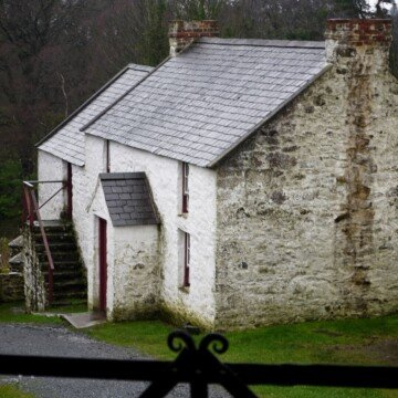 A two storey white stone farmhouse with slate roof as seen from the side