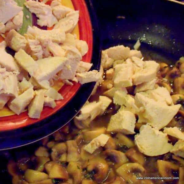 Adding poached chicken to mushrooms and wine in pan