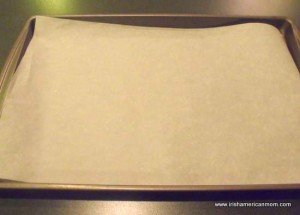 Lining a baking tray with parchment paper to make sausage rolls