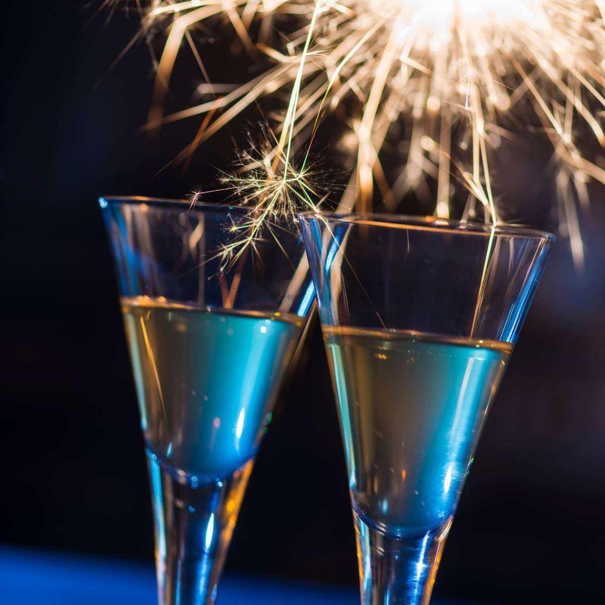Sparklers glisten at night over two glass flutes of champagne