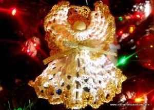 Christmas lights shine on a crochet angel ornament