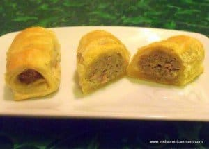 Three sausage rolls on a plate with one cut to show the interior