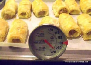 Checking the interior of pork sausage rolls are fully cooked using a food thermometer
