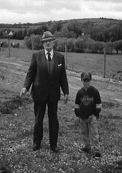 A man and boy standing in a field