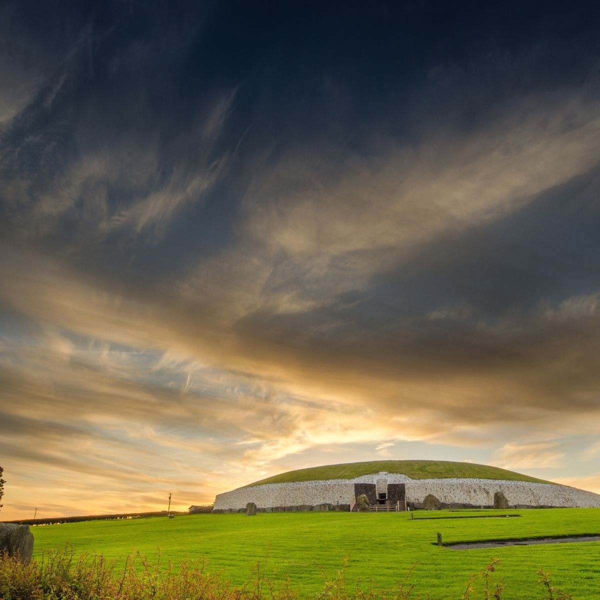The sun illuminates a large stone burial mound in a green field