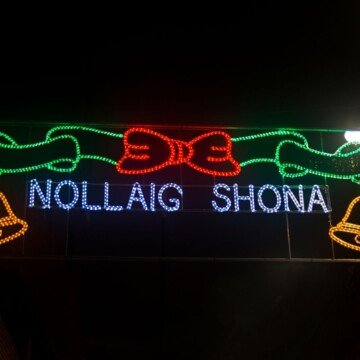 Blue text in an illuminated sign with a red and green bow against a black background