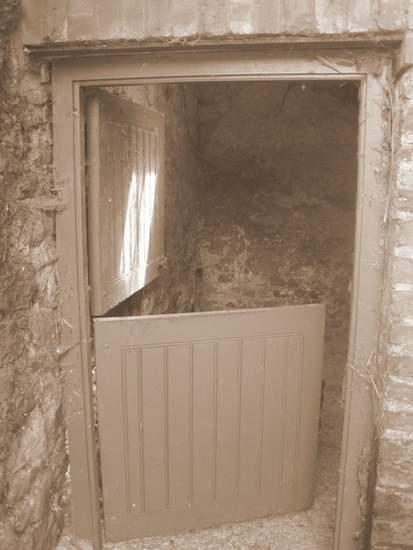 A black and white image of half door or Dutch door with the top half open