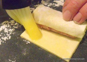 Using a brush to seal a sausage roll with egg wash