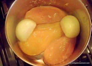 Three chicken breasts in a saucepan with a halved onion