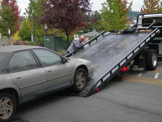 A tow truck lifting a car up a ramp