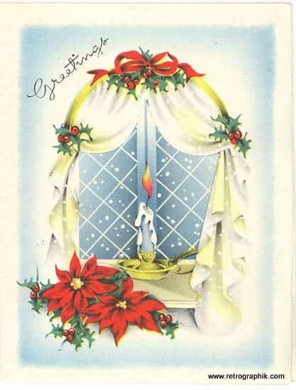 A candle burning in a cottage window with holly and poinsettia