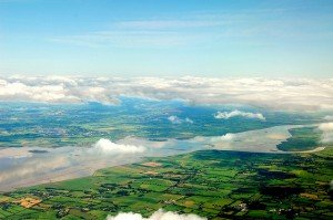 Above the clouds looking down on a patchwork pattern of green fields in Ireland
