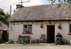 An old man sitting outside a thatched cottage with hanging flower baskets