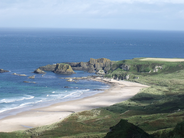 A sandy beach on the coastline with rocks and cliffs